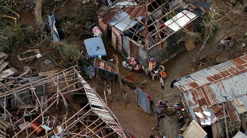 Des Haïtiens constatent les dégâts devant ces maisons dévastées à Jeremie.
