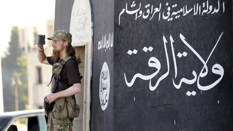 Un combattant étranger de l'État islamique filme une parade militaire.