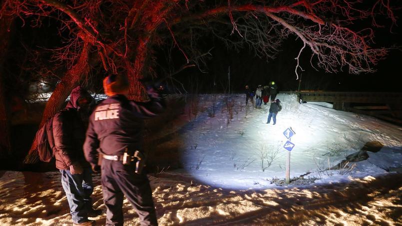 Des agents de la Gendarmerie royale du Canada (la police fédérale) éclairent un groupe de migrants arrivé à pied à la frontière canadienne.