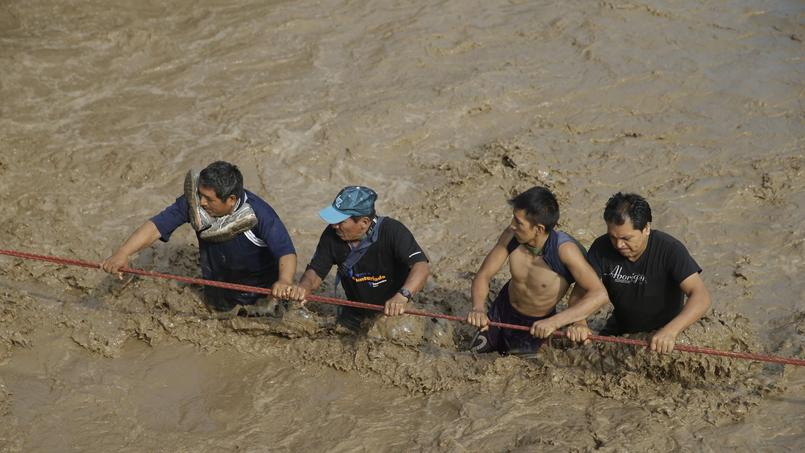 Les habitants traversent la rue à l'aide de cordes, pour ne pas tomber malgré le courant, à Lima, le 17 mars.