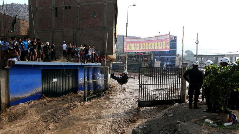 Des policiers traversent une rue avec une corde, à Huachipa (Lima), le 17 mars.