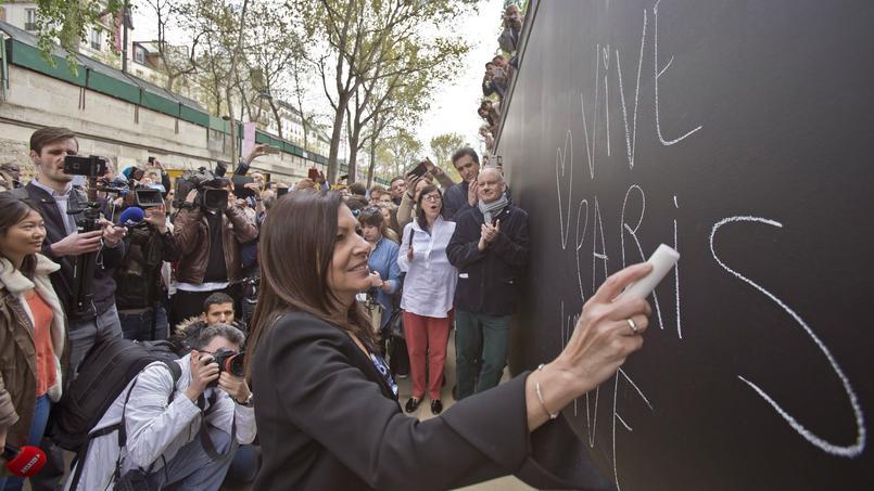 La maire de Paris Anne Hidalgo inscrivant vive Paris à la craie, avec un coeur.