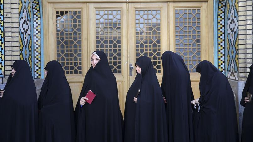 Des Iraniennes s'apprêtent à aller voter dans la ville de Qom.