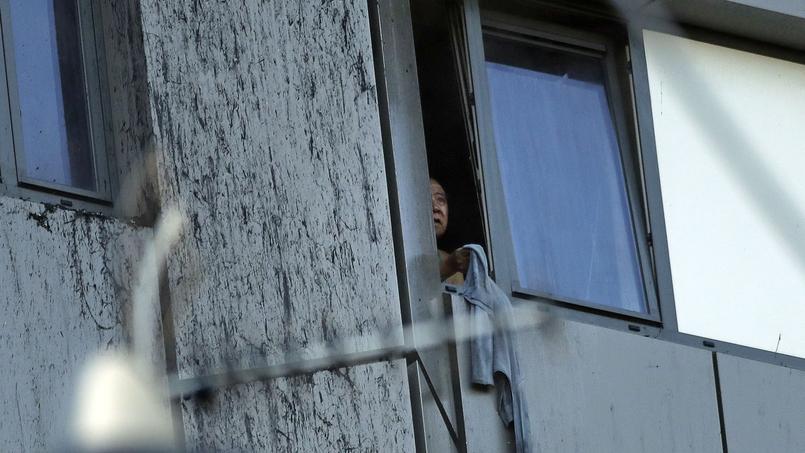 Une femme présente à l'intérieur de l'immeuble en flammes se signale à la fenêtre. Les pompiers oeuvrent à l'évacuation des personnes bloquées à l'intérieur.