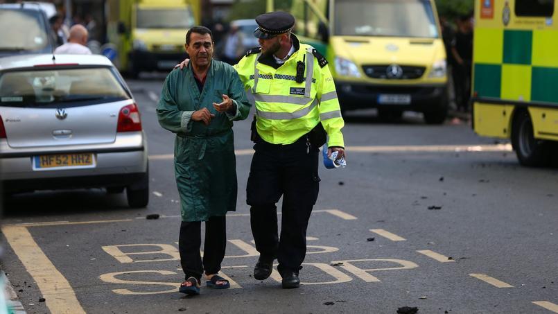 Un agent de police aide à l'évacuation d'un résident, mercredi matin.