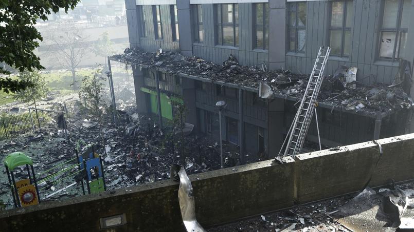 Les nombreux débris sont visibles au pied de l'immeuble, près d'une aire de jeu d'enfants.