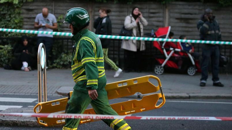 Un membre des services d'urgence transporte un brancard sur le site de l'incendie.