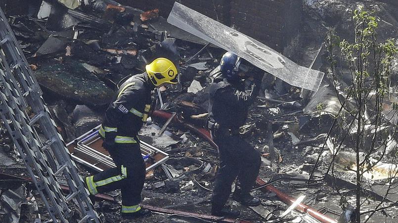 Des pompiers progressent au milieu des débris, mercredi matin.