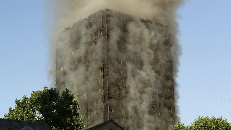 De la fumée s'échappe de la Grenfell Tower, mercredi matin, alors que le jour s'est levé.