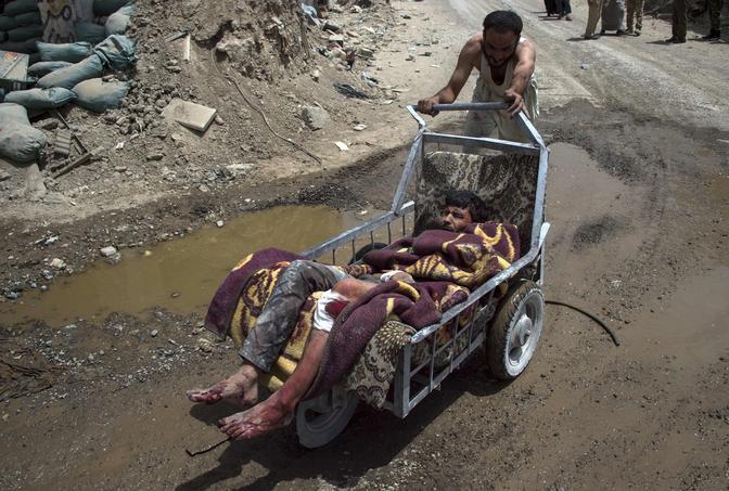 Un homme évacue un proche blessé à bord d'une remorque de fortune dans la vieille ville de Mossoul.