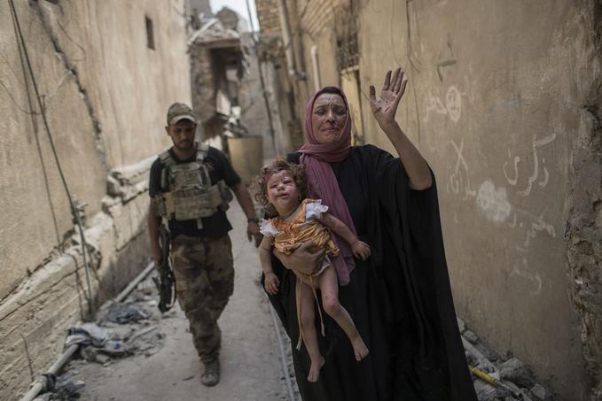 Une femme porte une petite fille blessée dans ses bras alors que les soldats des forces irakiennes poursuivent leur avancée dans les ruelles de la vieille ville de Mossoul.