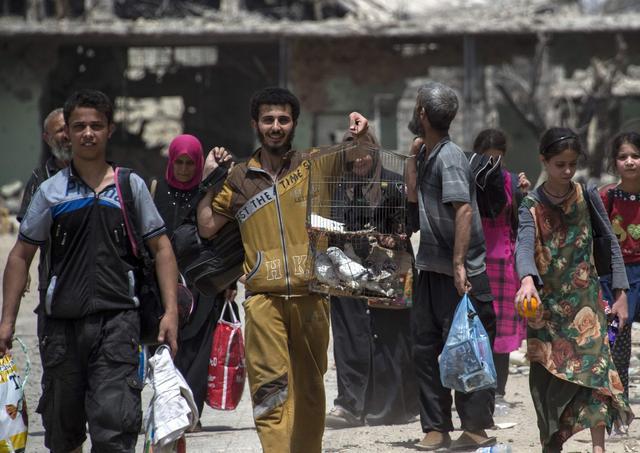 Un jeune homme arbore un large sourire et une cage à oiseaux alors qu'il évacue avec d'autres civils la vieille ville de Mossoul.