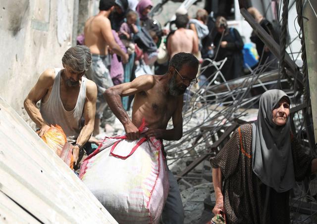 Des civils fuyant les combats emportent quelque affaires à travers les ruelles étroites et en partie détruites de la vieille ville de Mossoul.