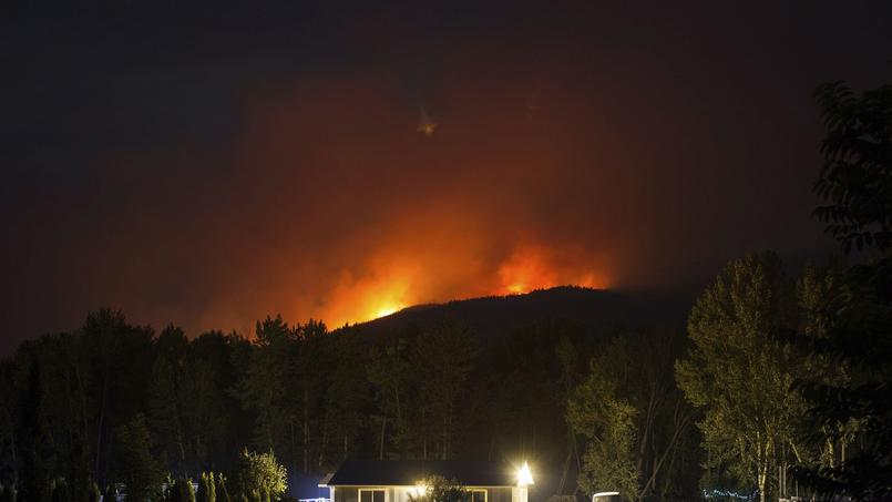 Les flammes illuminent Cache Creek, en Colombie Britannique. (Crédit photo: Darryl Dyck / The Canadian Press via AP)