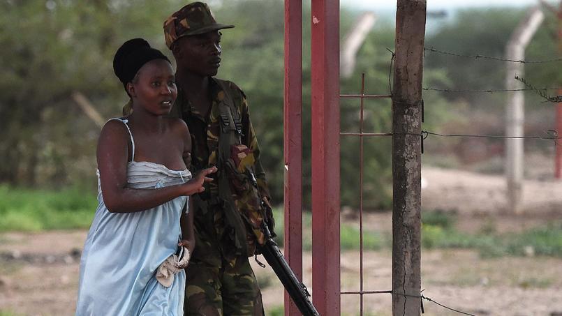 Un militaire kenyan aidant une étudiante à s'enfuir des lieux de l'attaque.