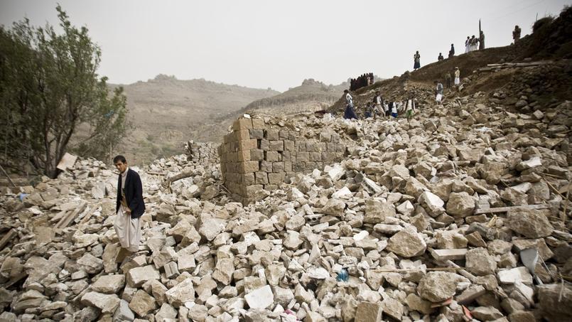 Un Yéménite se tient au milieu des ruines de maisons, détruites par des frappes menées par la coalition arabe, près de Sanaa, samedi.