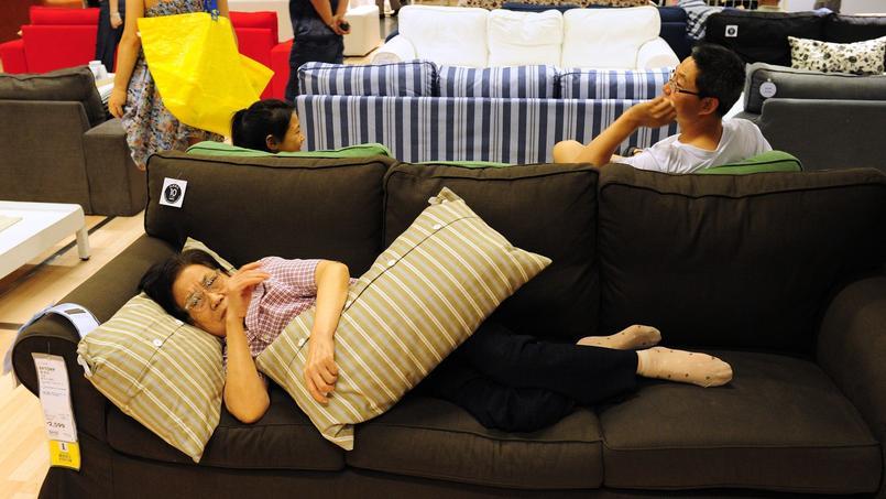 Une femme se repose sur un sofa dans un magasin Ikea à Pékin.