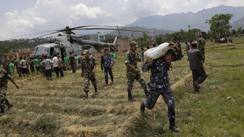 Des soldats népalais déchargent du matériel de premier secours transporté par l'armée indienne, le 27 avril 2015 à Trishuli Bazar au Népal.