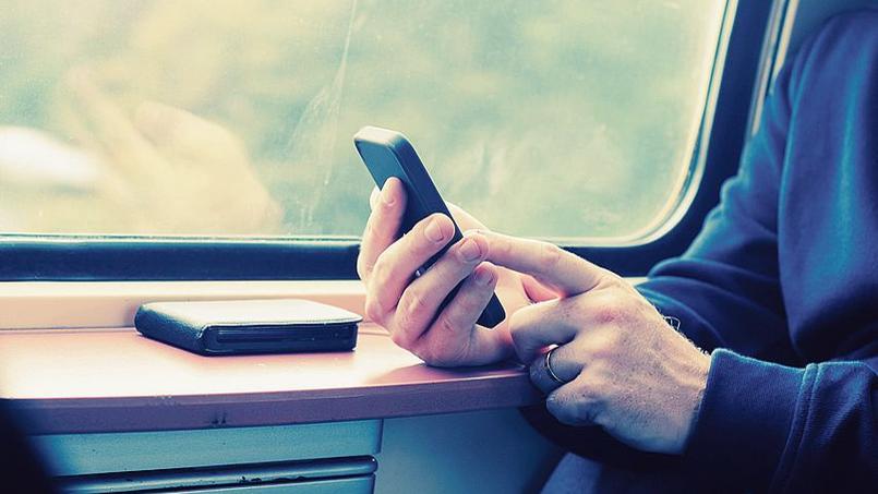 Un voyageur utilise son téléphone dans un train de la SNCF