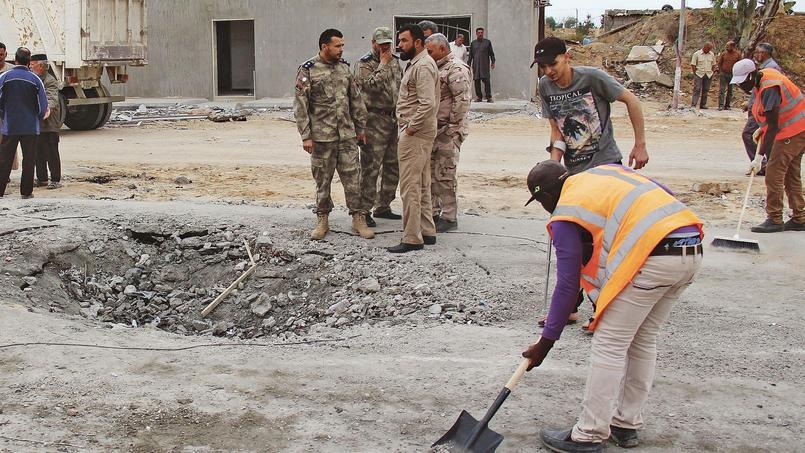 Des ouvriers nettoient la chaussée, dimanche, après l'attentat suicide à un check point à l'entrée ouest de Misrata.