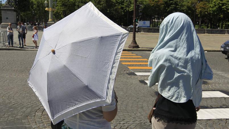 CANICULE A PARIS - Femmes se protégeant du soleil, en période de canicule, à Paris.Sébastien SORIANO / Le Figaro