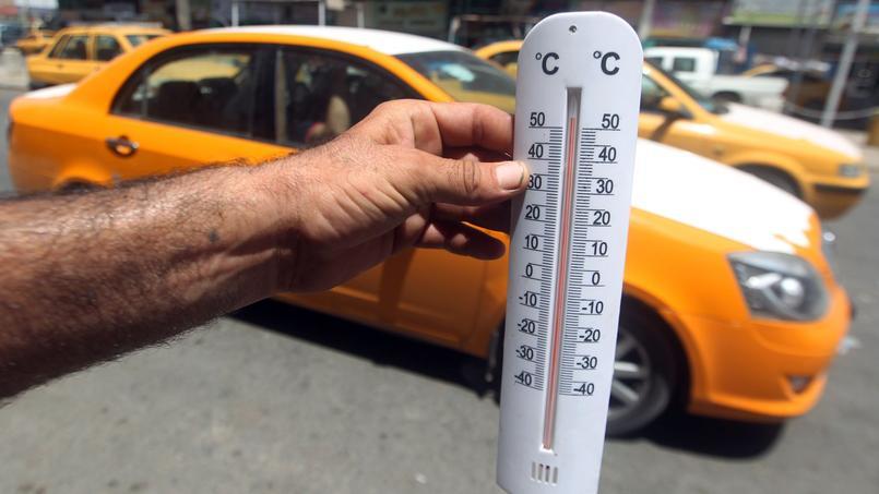 En Irak, un homme montre un thermomètre qui affiche plus de 50°c.