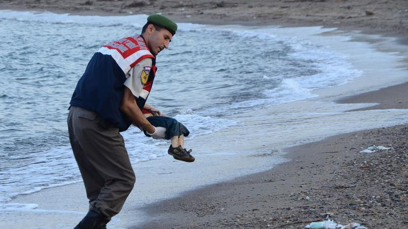 Un gendarme turc tient dans ses bras le corps d'un petit garçon syrien noyé en tentant de rejoindre la Grèce avec sa famille.