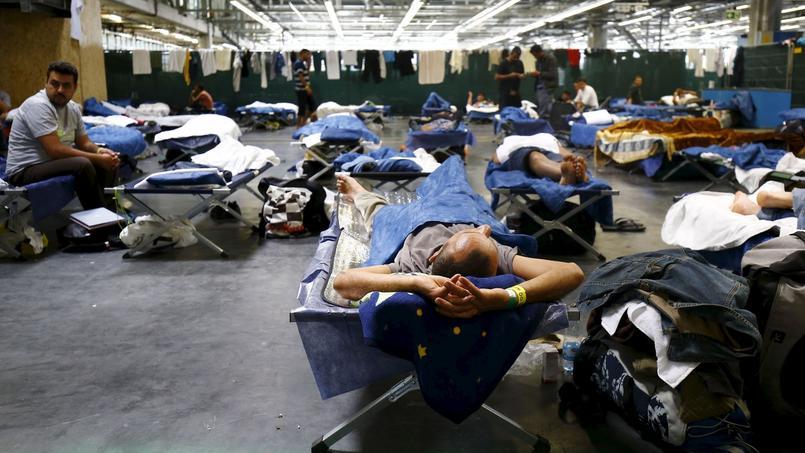 Des migrants se reposent sur des lits, dans un centre d'accueil à Francfort.