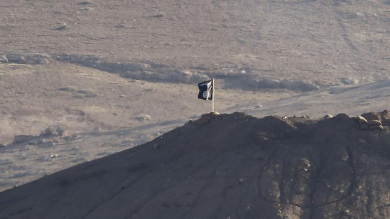 Un drapeau noir appartenant à l'Etat islamique flotte près de la ville de Kobané en Syrie le 6 octobre 2014.
