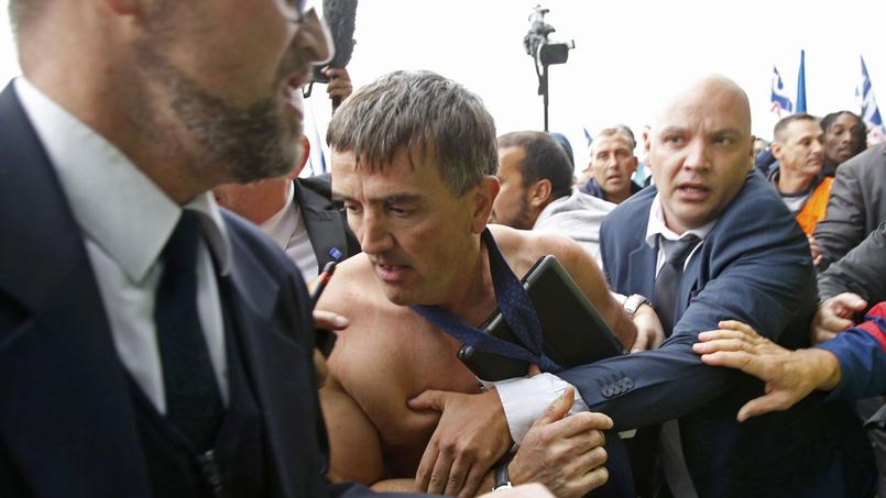 Xavier Broseta, DRH d'Air France, encadré par des agents de sécurité, tente d'échapper aux manifestants.