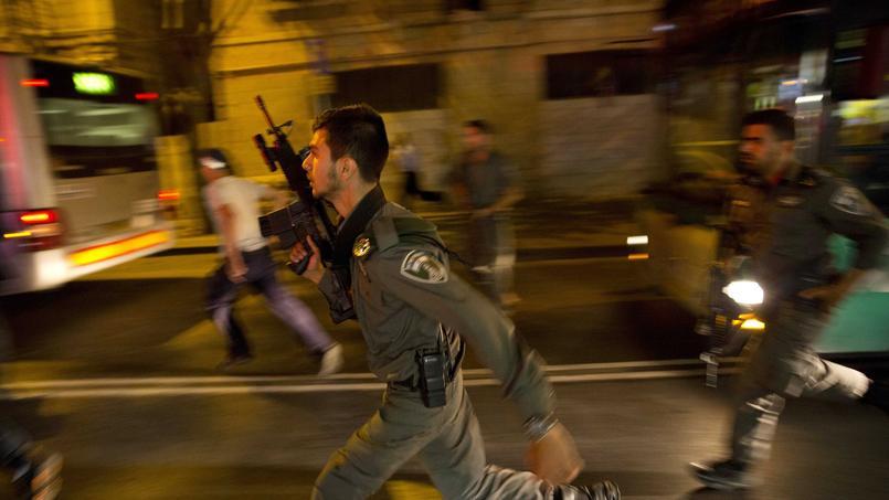 Des policiers israéliens prenant en chasse un potentiel suspect à Jérusalem.