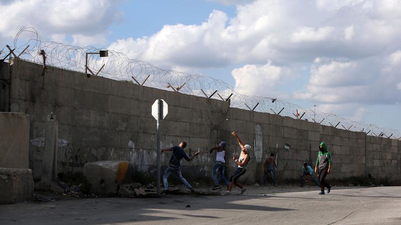 Des Palestiniens jettent des pierres aux soldats israéliens postés de l'autre côté du mur, samedi à Tulkarem.