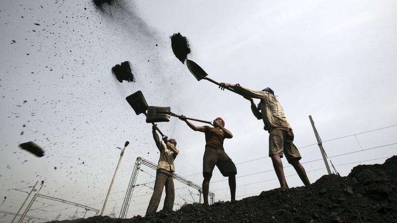 Ici, des travailleurs indiens chargeant un camion de charbon, à Jammu.