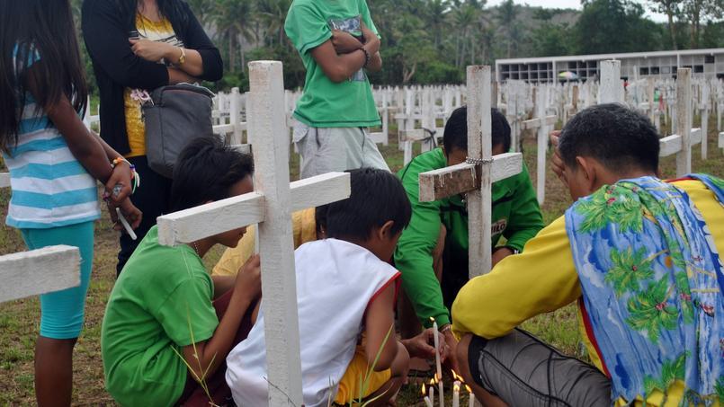 Une famille allume des bougies devant une tombe du cimetière de Tacloban, aux Philippines. Un lieu consacré aux victimes du typhon Haiyan, ayant provoqué 7350 morts et disparitions sur l'archipel, en 2013.