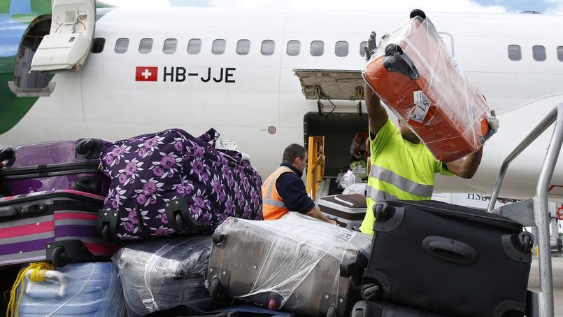 Des agents chargent des bagages dans un avion à l'aéroport de Roissy en août 2014.