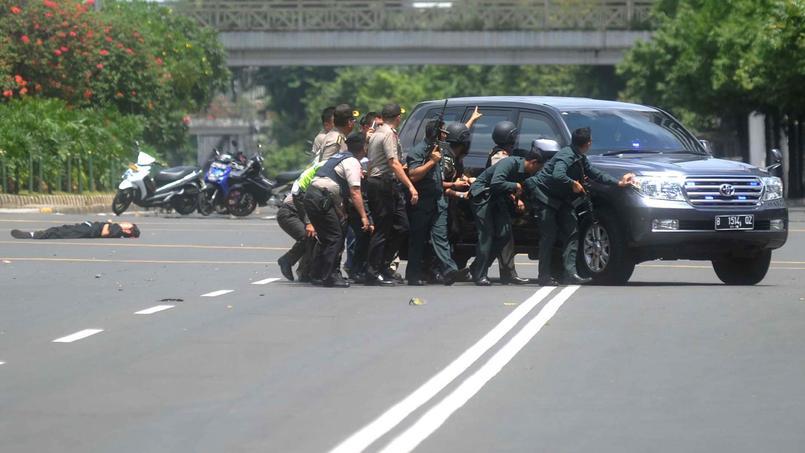 Les forces de l'ordre se mettent à couvert derrière un véhicule alors qu'elles essuient des tirs nourris de la part des assaillants, jeudi à Jakarta.