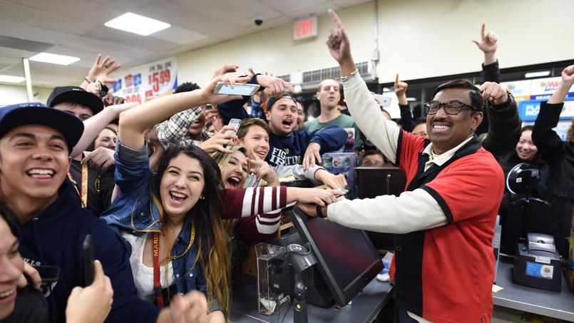 Un employé d'Eleven store célèbre avec des clients l'un des tickets gagnants du Powerball, le mercredi 13 janvier à Chino Hills, dans la banlieue californienne.