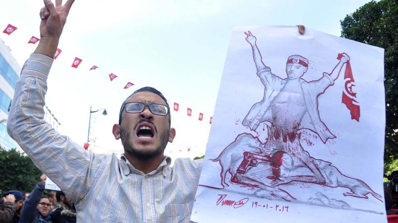 Un homme brandit un dessin lors d'une manifestation antigouvernementale, le 20 janvier 2016 à Tunis, en soutien aux protestations des habitants sans emploi de Kasserine, dans le centre du pays.