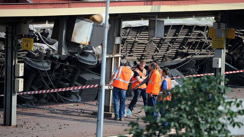 Sur le quai de la gare de Brétigny-sur-Orge, une voiture du train numéro 3657 Intercités couchée sur le flanc est inspectée le 13 juillet 2013. Le déraillement a fait sept morts et une trentaine de blessés.