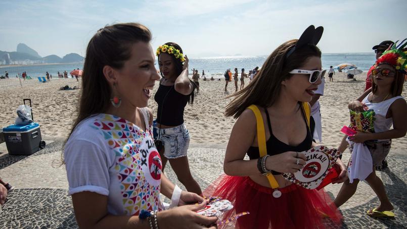 Des employés municipaux distribuent des prospectus pour la prévention contre le virus Zika sur la plage de Copacabana alors que le carnaval vient de débuter.