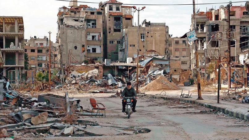 Un homme circule à moto entre les ruines de la ville d'Harasta, mercredi, dans la banlieue de Damas.