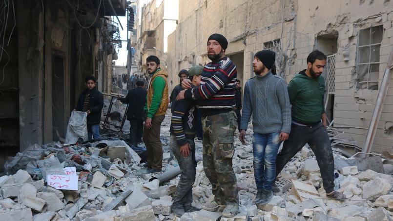 Des Syriens dans les ruines d'immeubles bombardés, dans le nord d'Alep.