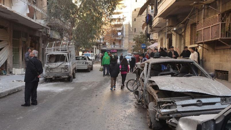 Des résidents regardent les dégâts après un bombardement rebelle dans le quartier de Suleimaniyeh tenu par le régime, dimanche à Alep, en Syrie.