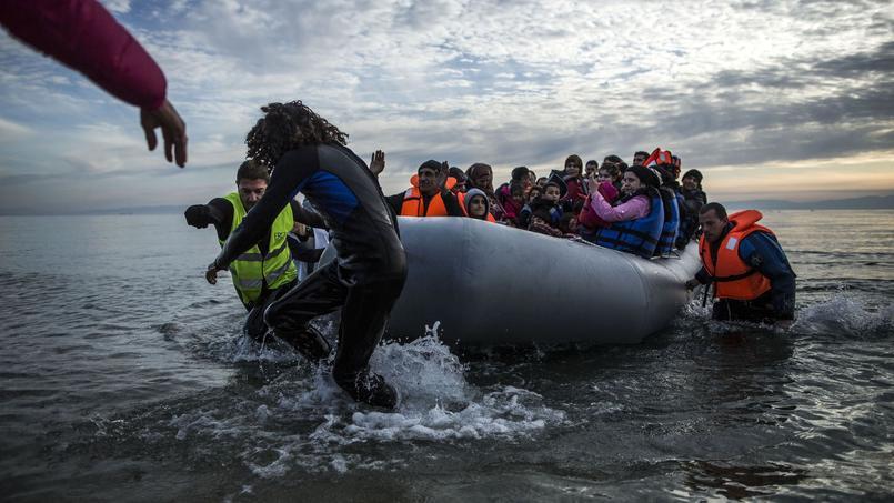 Des volontaires aident à l'accostage d'un canot de migrants arrivés, jeudi, jusqu'à l'île grecque de Lesbos depuis la Turquie.