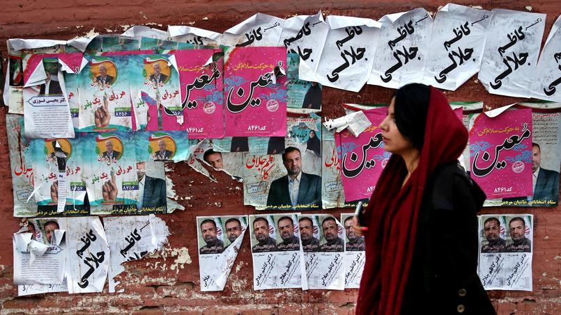 Une femme marche devant des affiches électorales placardées dans les rues de Téhéran.