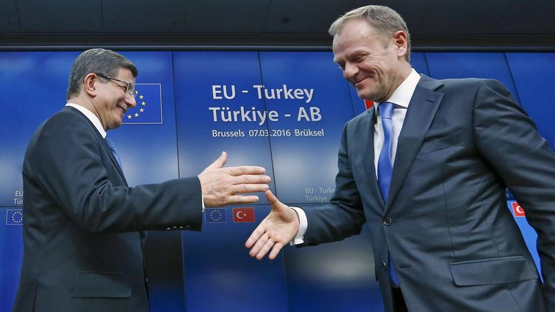 Ahmet Davutoglu, le premier ministre turc et Donald Tusk, président du Conseil européen, se serrent la main au terme du sommet européen qui s'est achevé dans la nuit de lundi à mardi.