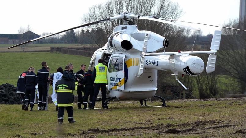 Les pompiers évacuent un enfant grièvement blessé après l'effondrement d'un stock de grains dans la ferme de Pont-sur-Sambre (Nord) mardi.