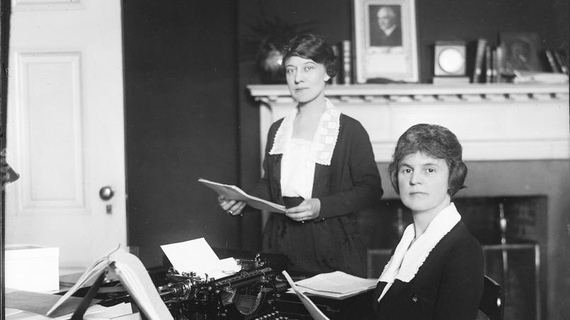Des femmes travaillant dans un bureau où est affiché un portrait du président Warren Harding. La Journée internationale des droits des femmes est née au début du XXe siècle avec la mobilisation de femmes ouvrières.