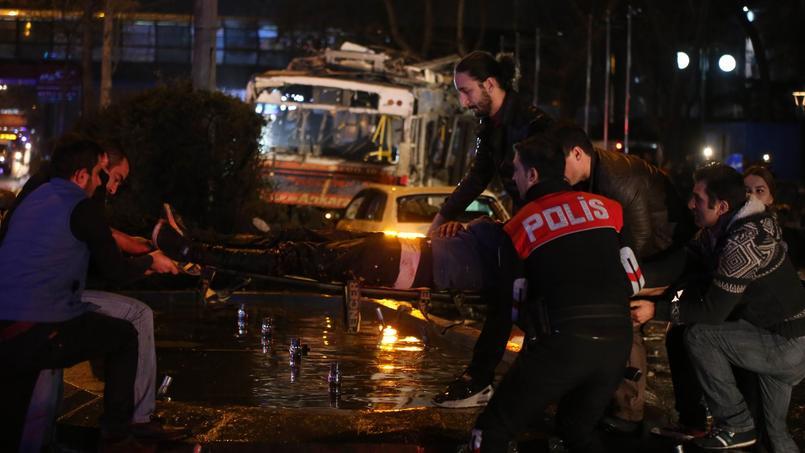 Un homme blessé lors de l'explosion de la voiture piégée est secouru dimanche, près de la place Kizilay, à Ankara. Au fond, le bus visé par l'attentat.