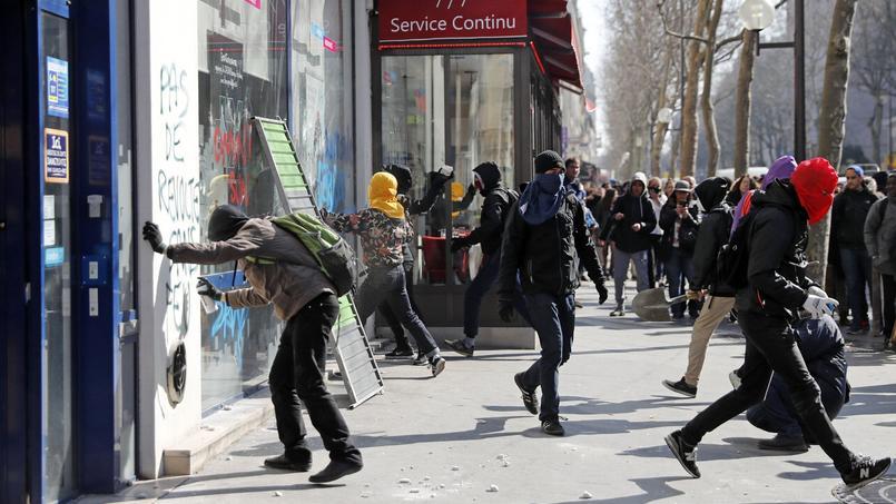 Des jeunes cagoulés taguent les vitres d'une banque en marge du cortège parisien.